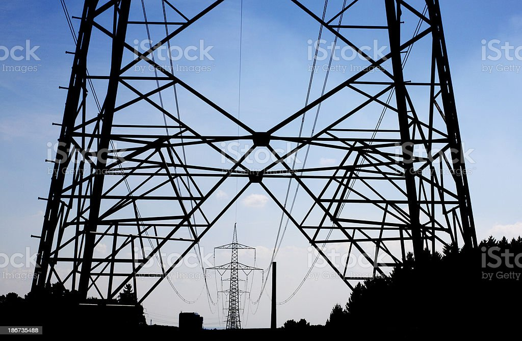 High voltage pylon with power plant in the background royalty-free stock photo
