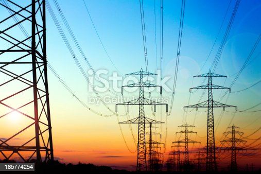 High voltage pylons in the evening sun. a large number of pylons in the back light of the setting evening sun in a row. On the left, a large pylon. The sun shines through. Clear, blue sky in the upper range, In the lower area of orange, black, outline