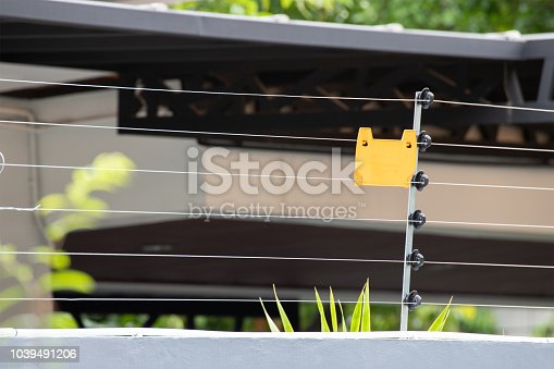 istock high voltage security fence on house wall with blank yellow plastice sign. 1039491206