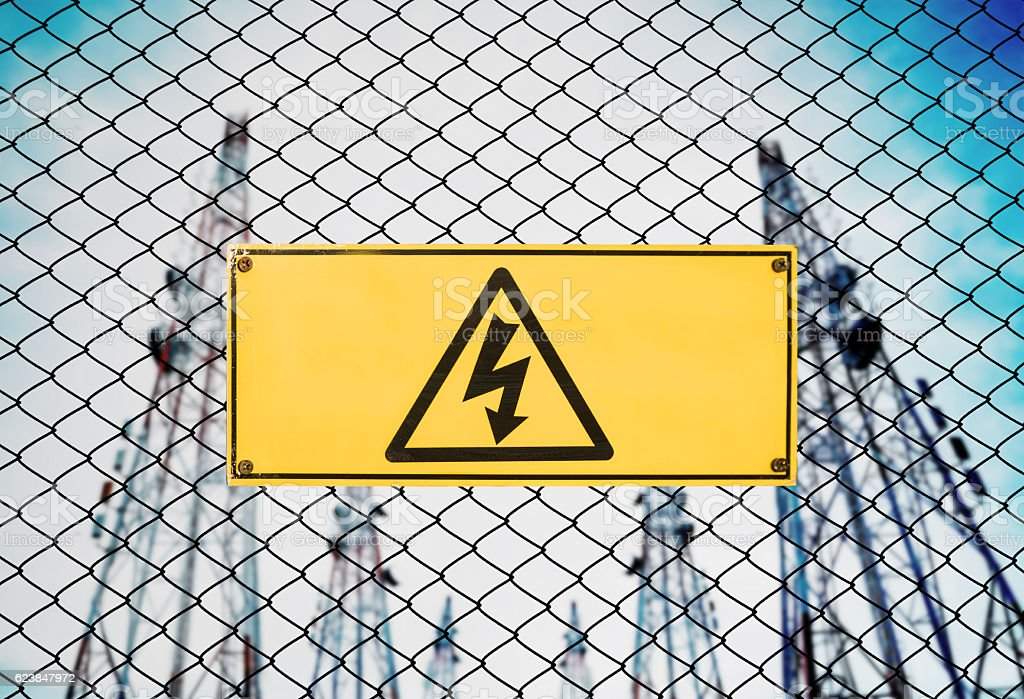 High Voltage Sign and Symbol Caution Signboard on Fence Wire stock photo