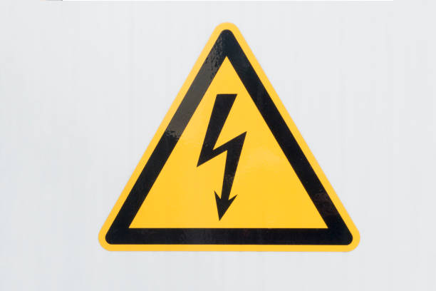 high voltage sign close up - on gray background - symbol stock pictures, royalty-free photos & images