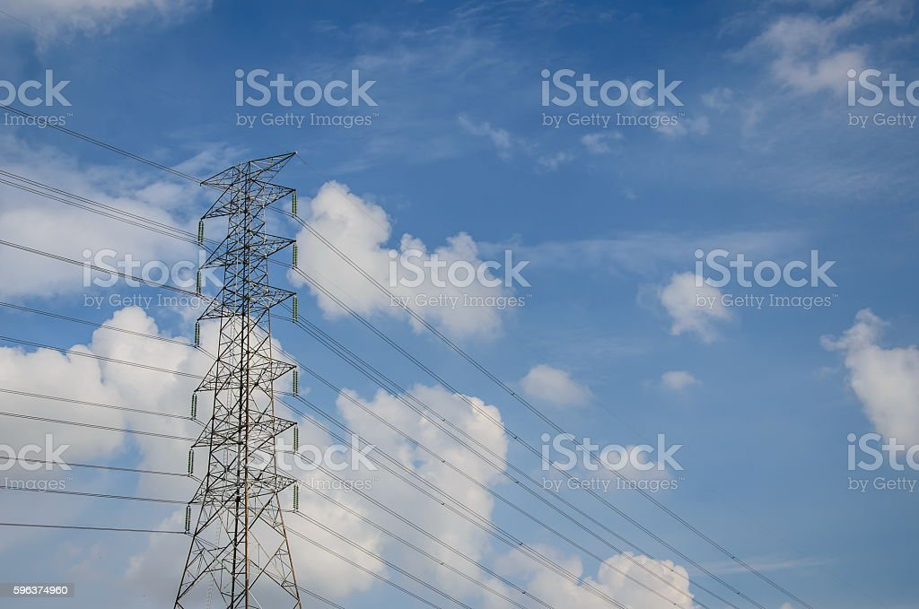High voltage tower and electric line over cloudy blue sky stock photo