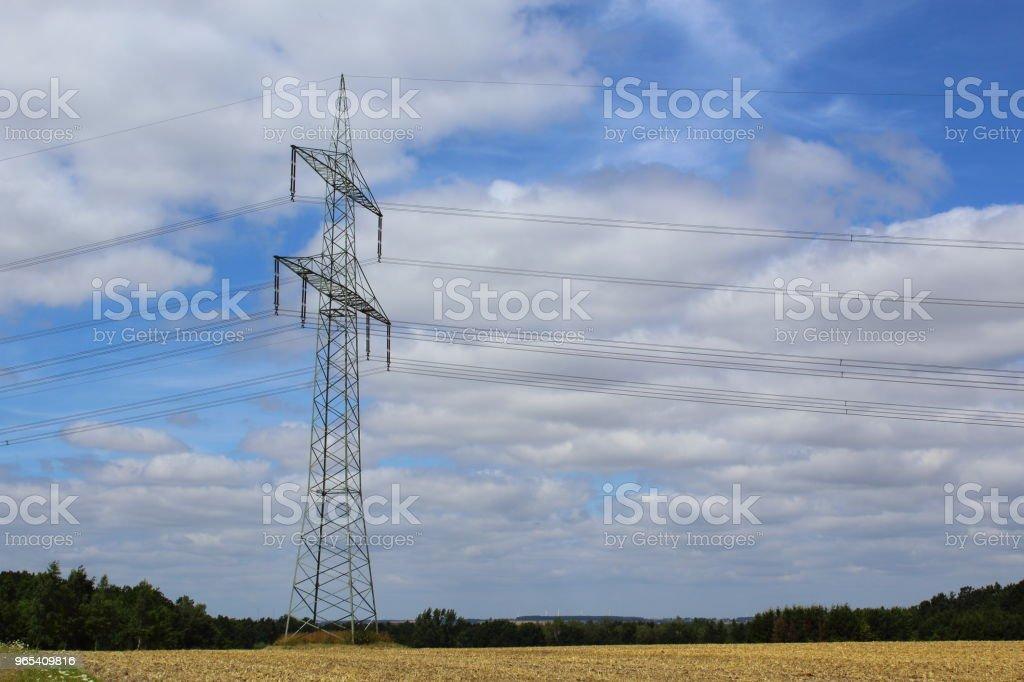 tour de transmission de haute tension sur un champ - Photo de Alimentation électrique libre de droits