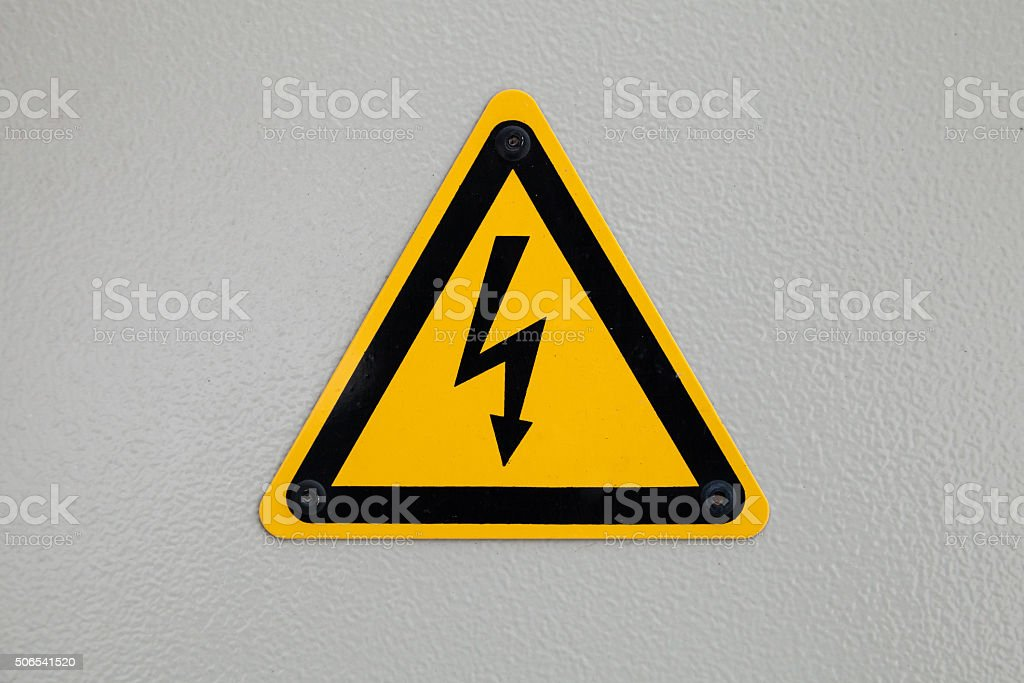 High voltage triangle warning sign mounted on gray stock photo
