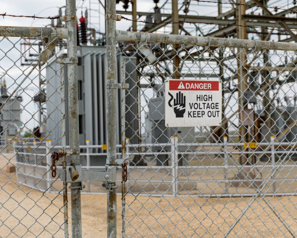 High voltage warning sign on locked gate at electrical substation stock photo