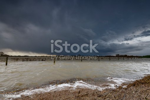 High water level in the river IJssel during a storm with clouds blowing over the landscape in the Vreugderijkwerwaard nature reserve near Zwolle in Overijssel, The Netherlands.