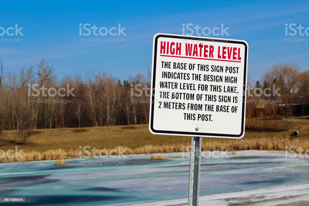 High water level sign along a storm drainage pond stock photo