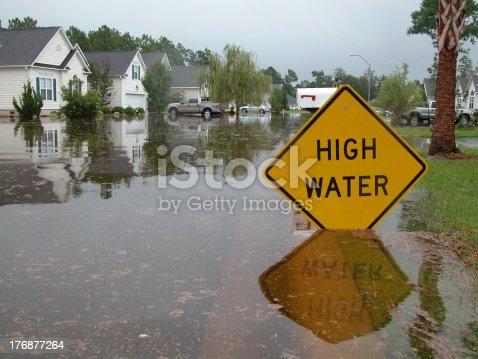 Neighborhood flooded.  Sign warns of high water.