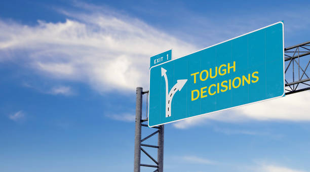 high way sign with motivation, warning or advice message about tough decisions stock photo