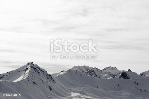 High winter mountains with snowy slopes and sunlit cloudy sky at morning. Italian Alps. Livigno, region of Lombardy, Italy, Europe. Black and white toned landscape.
