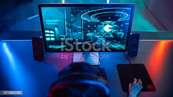 istock High-angle Shot of the Professional Gamer Playing in First-Person Shooter Online Video Game on His Personal Computer. Room Lit by Neon Lamps in Retro Arcade Style. 1010650382