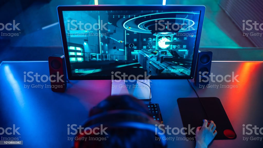 High-angle Shot of the Professional Gamer Playing in First-Person Shooter Online Video Game on His Personal Computer. Room Lit by Neon Lamps in Retro Arcade Style. stock photo