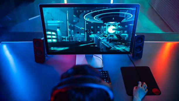 high-angle shot of the professional gamer playing in first-person shooter online video game on his personal computer. room lit by neon lamps in retro arcade style. - esports stock photos and pictures
