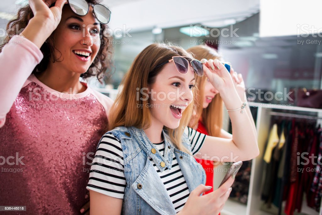 High-angle shot of young stylish female friends wearing trendy sunglasses and clothes having fun in shopping center stock photo