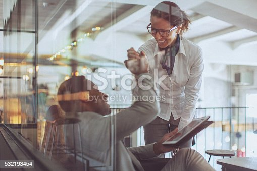 Young businessman and businesswoman giving each other a high five in a modern office space