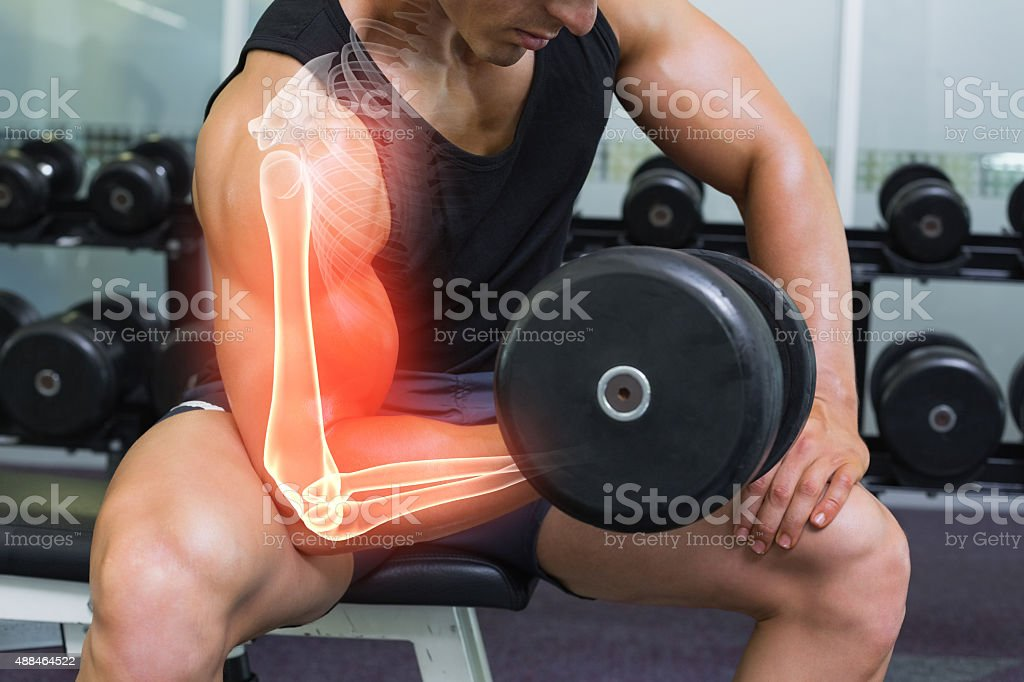 Highlighted arm of strong man lifting weights stock photo