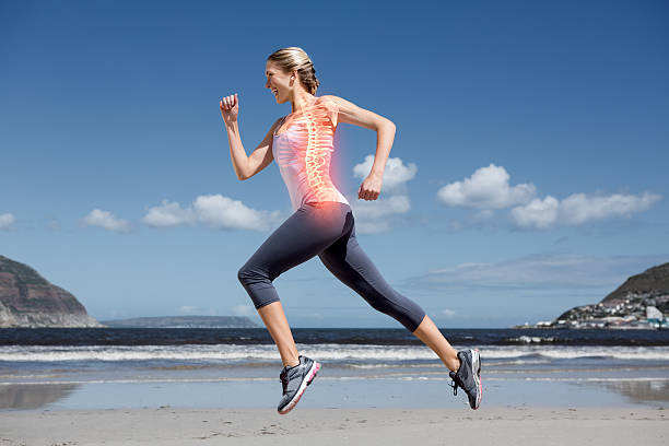 Highlighted back bones of jogging woman on beach stock photo