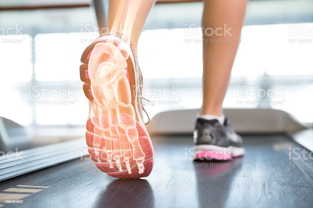 Highlighted foot of woman on treadmill stock photo