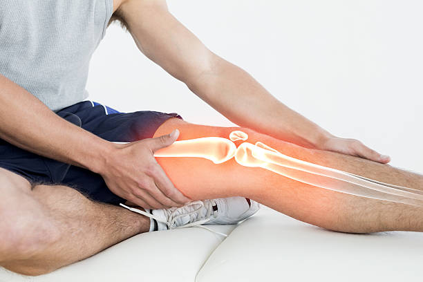 Highlighted knee of injured man stock photo