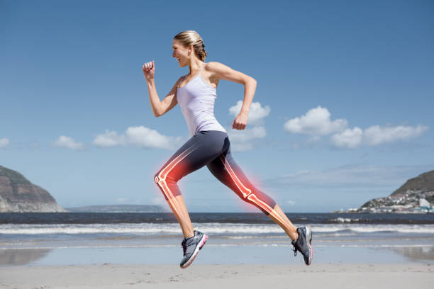Highlighted leg bones of jogging woman on beach stock photo