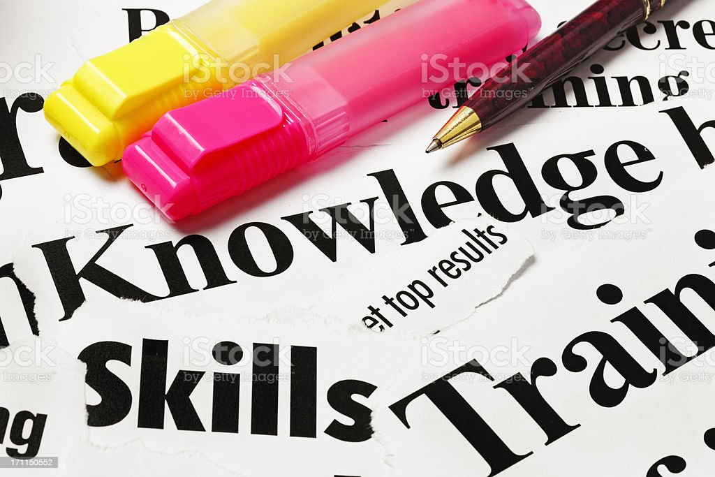 Highlighter and pen sit on cuttings concerning knowledge, training stock photo