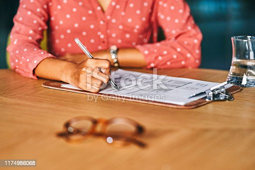 Closeup shot of an unrecognisable businesswoman filling in paperwork in an office at night