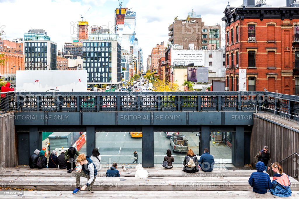 Highline, high line, urban garden in NYC with many people tourists, sitting in Chelsea West Side by Hudson Yards looking at view under stock photo