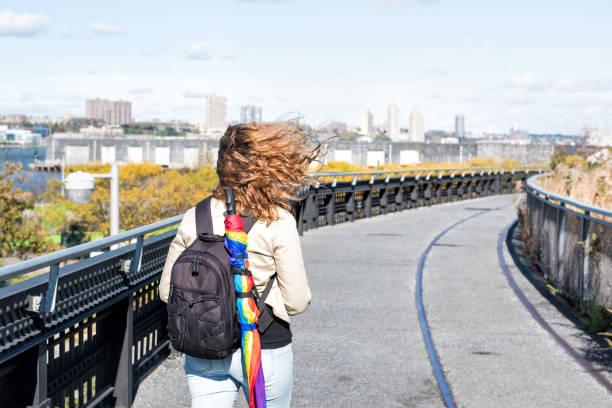 """ハイライン、ハイライン、lgbt lgbtq 傘、バックパック ハドソンのヤードでチェルシー西側で秋の虹と一緒に歩いている人観光客女性の都市のニューヨークの秋の黄色の黄金の木 - """"gender fluid"""" ストックフォトと画像"""
