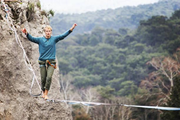 highliner an einem seil. highline auf einem hintergrund von bergen. extremsport auf die natur. balancieren auf der schlinge. gleichgewicht in der höhe. - slackline stock-fotos und bilder