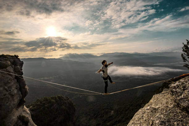 Highlining in the mountains at sunrise stock photo