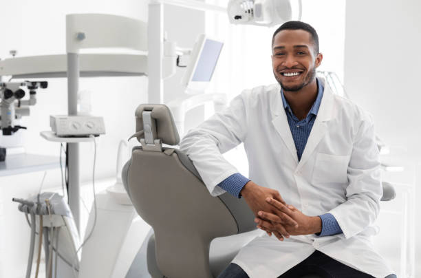 Highly qualified young dentist posing at modern clinic Highly qualified young black dentist posing at clinic over modern cabinet, empty space dentist stock pictures, royalty-free photos & images