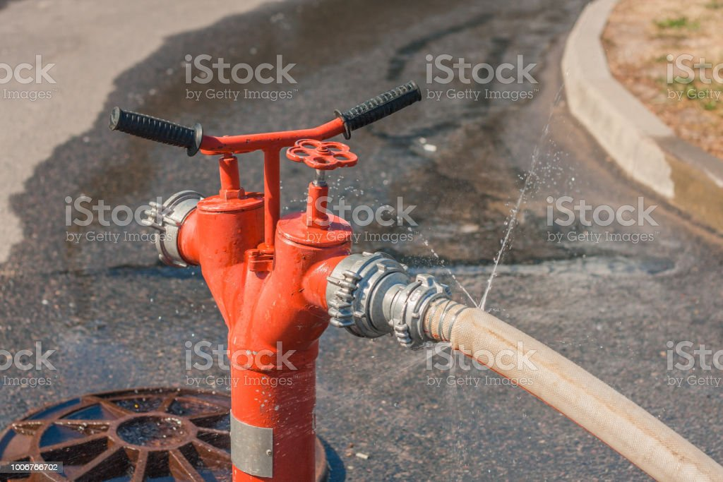 High-pressure water jets from a damaged fire hose stock photo