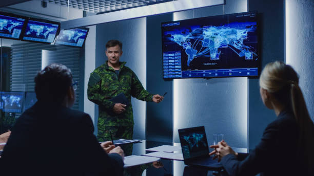 High-Ranking Military Man holds a Briefing to a Team of Government Agents and Politicians, Shows Satellite Surveillance Footage. High-Ranking Military Man holds a Briefing to a Team of Government Agents and Politicians, Shows Satellite Surveillance Footage. defend stock pictures, royalty-free photos & images