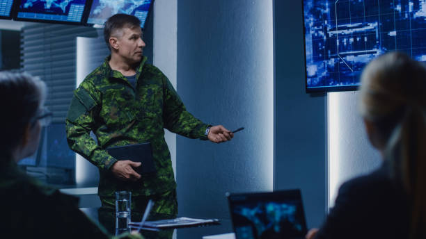 High-Ranking Military Man holds a Briefing to a Team of Government Agents and Politicians, Shows Satellite Surveillance Footage. High-Ranking Military Man holds a Briefing to a Team of Government Agents and Politicians, Shows Satellite Surveillance Footage. counter terrorism stock pictures, royalty-free photos & images