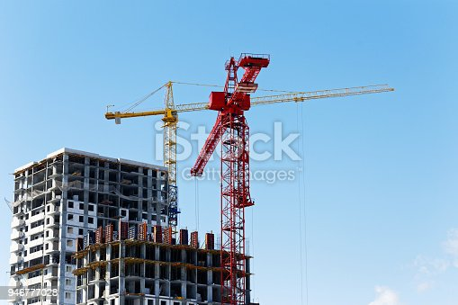 High-rise buildings under construction with red and yellow building cranes against the blue sky