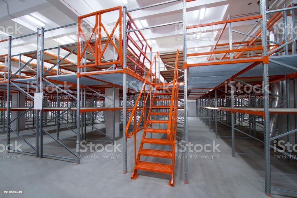 High-rise racks with ladder. Mezzanine shelves. stock photo