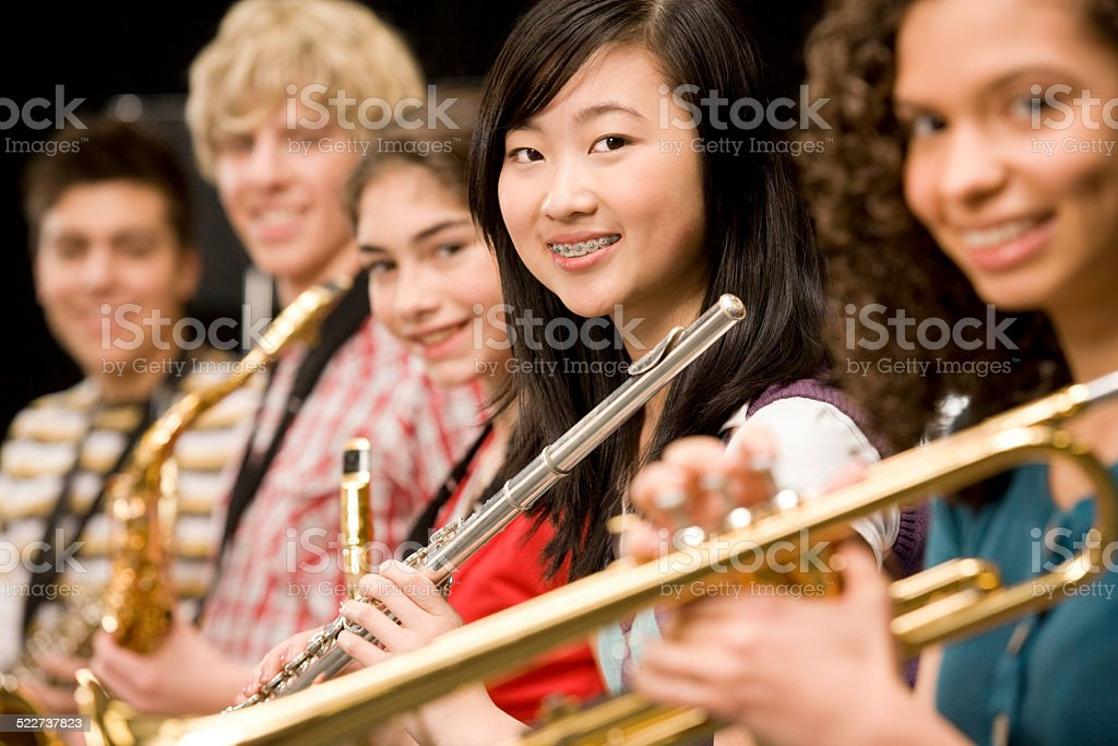High-school girl playing flute with schoolmates stock photo