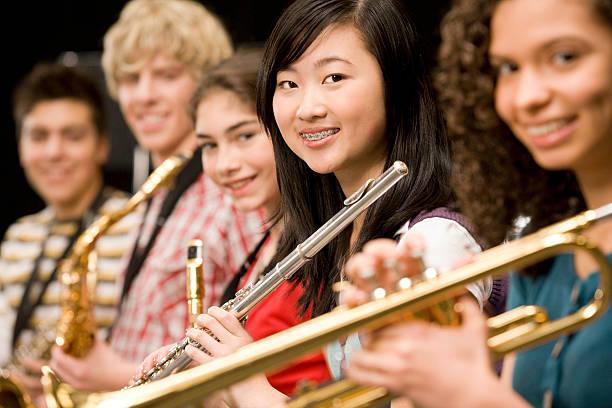 High-school-Mädchen spielt Flöte mit schoolmates – Foto