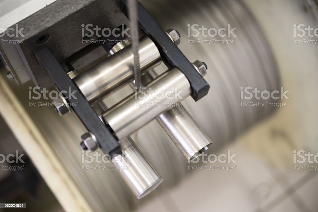 High-speed braiding machine. Winding the finished braid over the reel stock photo