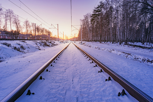 Highspeed train moves fast through the station at winter sunset.