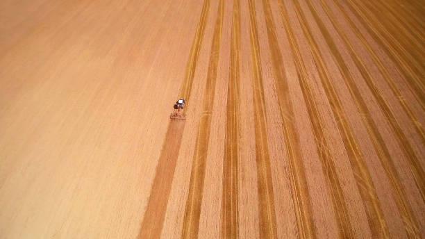 höhenansicht des traktors, der das feld pflüge lässt - aerial view soil germany stock-fotos und bilder