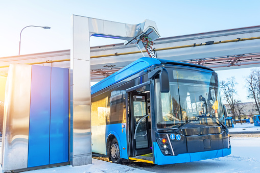 High-voltage electric charging station for charging electric buses at the final stop of the city route. Bus at the final stop with an open door