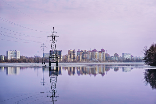 High-voltage power line over the wide lake and city in the distance. Sunset and reflection in water. Electrical conductor. Technology in the city. Voronezh, Russia.