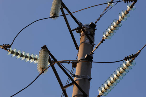 High-voltage towers against the blue sky. High-voltage electrical insulator. Electric hub on pole. Wires of high voltage in sky. stock photo