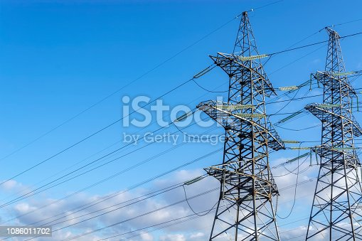 Two supports of high-voltage transmission line with electric power wires on the blue sky background.