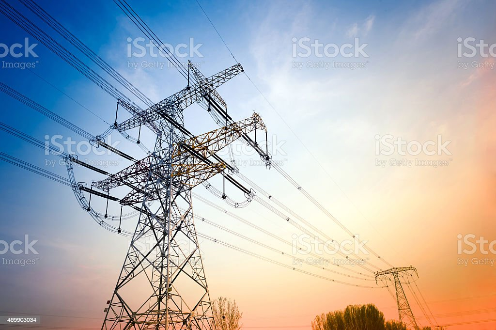 High-voltage wire tower at dusk stock photo