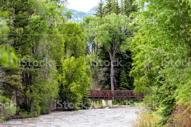 Photo of Highway 133 in Redstone, Colorado during summer with red bridge on Crystal river by trees