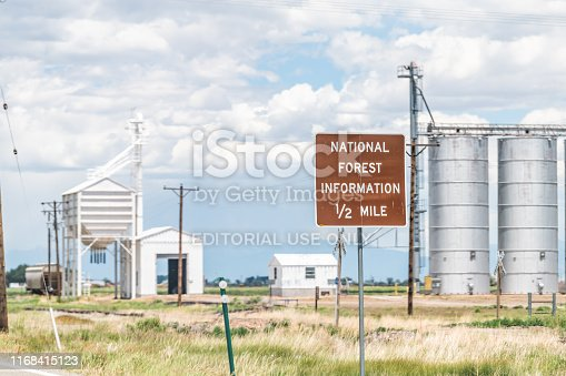 Romeo, USA - June 20, 2019: Highway 285 in Colorado with old vintage town industrial building and sign for National Forest Information
