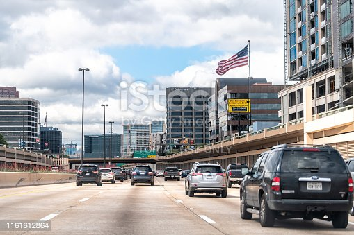istock Highway 75 in city in summer with cars in traffic with American Flag waving in downtown 1161612864
