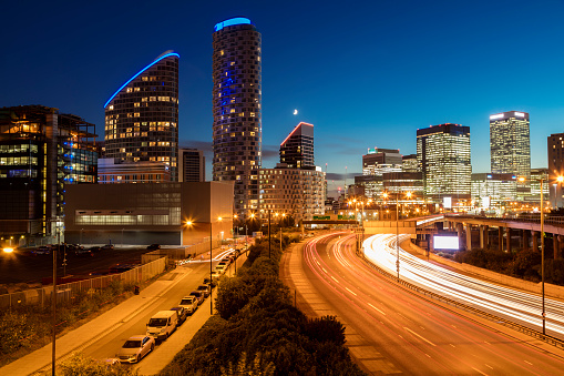Busy highway with light trails from traffic in Docklands, Canary Wharf, Dosklands, London, United Kingdom. Residential and financial buildings are visible in the background against deep blue sky at dusk. Long exposure with tripod.